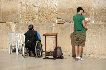 A disabled man in a wheelchair, praying at the Western Wall in Jerusalem.