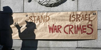 Protesters are silhouetted against an anti-Israel sign during a small demonstration outside the Art Gallery in downtown Vancouver, Canada. July 31, 2006.