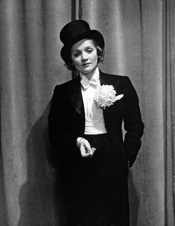 Marlene Dietrich in a 1929 photograph by Alfred Eisenstaedt, werting white button shirt , blackk suit with large white boutonniere, top hat, one hand in a jacket pocket, one held up.