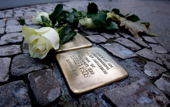 A rose lies next to a memorial stone commemorating Holocaust victim Rosa Lesser in front of her former home in Berlin. Munich may consider installing similar memorial stones  to individual victims.