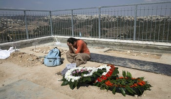 A woman mourns near the grave of Eitam and Na'ama Henkin, who were shot and killed while driving through the West Bank with their children, after their funeral in Jerusalem October 2, 2015.