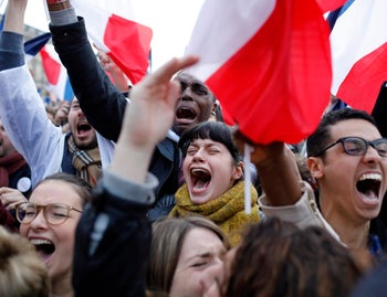 Supporters of French centrist presidential candidate Emmanuel Macron react to his win outside the Louvre museum in Paris, May 7, 2017.