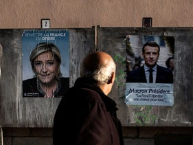 A man walking past campaign posters of French presidential election candidates Marine Le Pen and Emmanuel Macron, April 21, 2017.