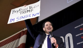 Republican U.S. presidential candidate Marco Rubio holds up a supporter's sign at a campaign rally on the eve of Super Tuesday in Oklahoma City, Oklahoma February 29, 2016.