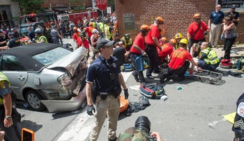 A woman receives first-aid after a car plows into a crowd of protesters in Charlottesville, VA on August 12, 2017.