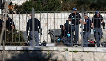 Israeli security forces and emergency personnel stand next to the body of a Palestinian man following an attack at Damascus Gate, a main entrance to Jerusalem's Old City on February 3, 2016.