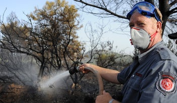 A fireman puts out a wildfire near the Gilon junction in northern Israel, Oct. 22, 2011.
