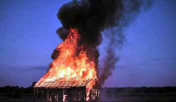 Polish performance artist Rafal Betlejemski burning down a barn to commemorate the Jedwabne pogrom.
