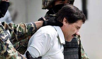 An archive photo showing drug lord Joaquin Guzman in the custody of two Mexican marines.