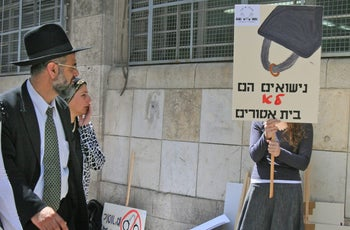 """""""Marriage is not a prison"""": A religious couple walks by a demonstrator protesting Jewish religious divorce policy in Jerusalem."""