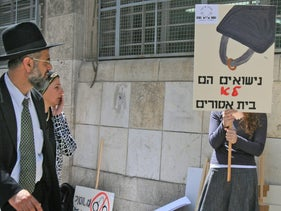 """Marriage is not a prison"": A religious couple walks by a demonstrator protesting Jewish religious divorce policy in Jerusalem."