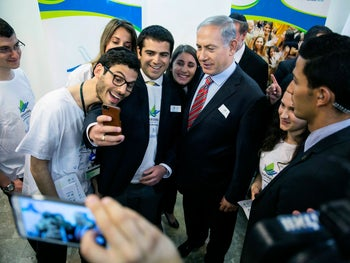 Prime Minister Benjamin Netanyahu, center, poses for a photo with members of Masa, a program which provides educational trips for young Jewish adults, in Jerusalem, Sunday, March 30, 2014.