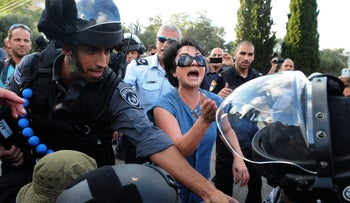 Knesset Member Haneen Zoabi attending a rally in Haifa against the Israeli military operation in Gaza, July 18, 2014, surrounded by police.