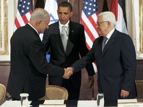 Obama watches Prime Minister Netanyahu and Palestinian President Abbas as they shake hands at a trilateral meeting at the Waldorf Astoria Hotel in New York, Sept. 25, 2009.