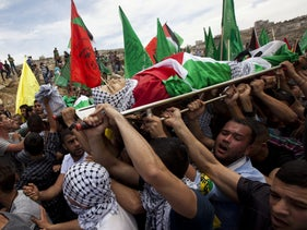 Mourners carrying the body of Palestinian teen Nadim Nuwara, who was killed in a clash with Israeli troops on May 15, during his funeral in Ramallah, May 16, 2014.