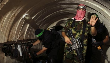 A Palestinian fighter from the Iz al-Din al-Qassam Brigades, the armed wing of the Hamas movement, gestures inside an underground tunnel in Gaza, August 18, 2014.