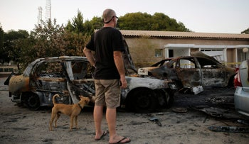 A man looks at cars destroyed by mortar fire in Kibbutz Nahal Oz, on the Gaza border with Israel, during the 2014 conflict.