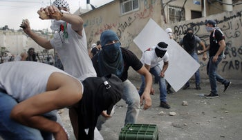 Palestinian youth hurl stones at Israeli policemen in protest against the death of a teenager, in Wadi Joz neighborhood of East Jerusalem, September 7, 2014.