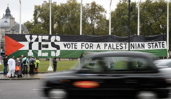 A London taxi drives by a pro-Palestinian rally in Parliament Square, London, October 13, 2014.