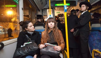 Secular women sit on a bus with ultra-orthodox men in Jerusalem.
