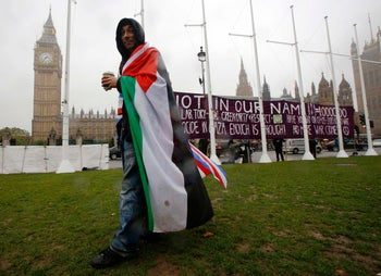 A pro-Palestinian supporter wears a Palestinian and Union flag outside the Houses of Parliament in London, just before a vote passed recognizing the State of Palestine. October 13, 2014