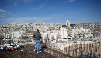 A laborer stands on an apartment building under construction in a Jewish settlement known to Israelis as Har Homa and to Palestinians as Jabal Abu Ghneim, October 28, 2014.