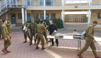 Yashar Lachayal's Leon Blankrot, in black, handing out aid packages with cold-weather gear to an all-Druze Israeli army unit, November 28, 2014.
