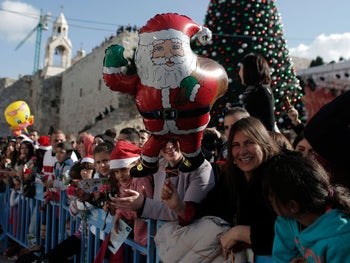 People gather to watch Christmas celebrations in Manger Square outside the Church of the Nativity as Christians gather for Christmas celebrations in the West Bank city of Bethlehem, December 24, 2014.
