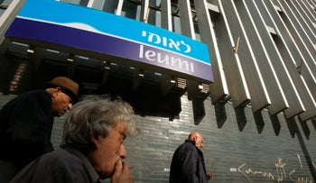 People walk past a branch of Bank Leumi in Tel Aviv in this February 18, 2009 file photo.
