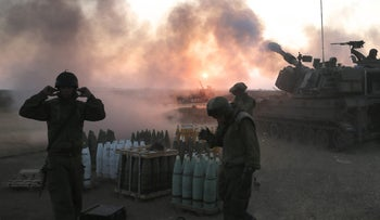 Israeli soldiers fire artillery towards the Gaza Strip in Operation Protective Edge.