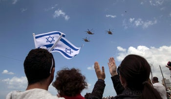 People watch from a Tel Aviv beach as Israeli Air Force helicopters fly over the Mediterranean Sea, during Independence Day celebrations, April 23, 2015.