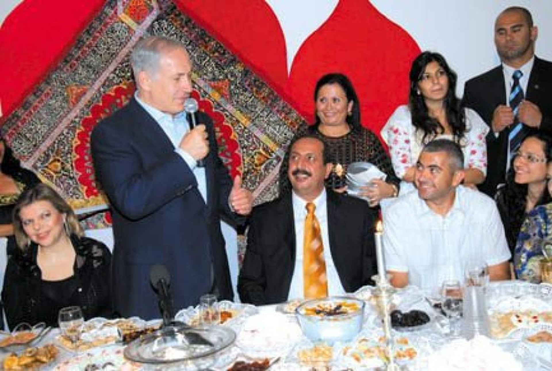 Benjamin Netanyahu, standing, and Avi Fahima, bottom right in white shirt, at an event in Or Akiva, 2010.