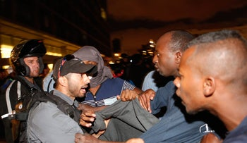 Police officers and Ethiopian-Israeli protesters clash in front of Tel Aviv city hall.