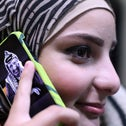 A Palestinian young woman uses a mobile phone bearing a portrait of late Palestinian leader Yasser Arafat on November 5, 2014, in the West Bank city of Ramallah.