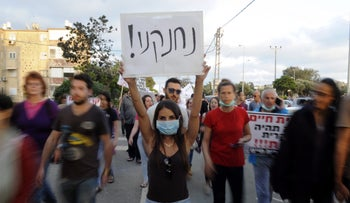 """A demonstrator holding up a sign reading """"we're choking!"""" during a protest against air pollution in Haifa, May 3, 2015."""