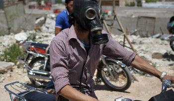 A man on a motorcycle wears a gas mask after a reported chlorine gas attack in Syria's Idlib province in May.