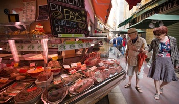 Shoppers browse meat for sale in a butcher's counter in an open air market in the old town in Nice, France, May 14, 2015.