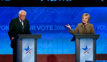 Bernie Sanders, left, listens as Hillary Clinton speaks during a Democratic presidential primary debate Saturday, December 19, 2015, at Saint Anselm College in Manchester, New Hampshire.