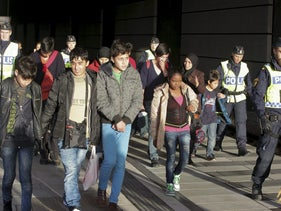 A group of migrants, coming off an incoming train, are seen next to police on the platform at the Swedish end of the bridge between Sweden and Denmark, Malmo, Sweden, November 12, 2015.