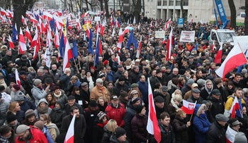 Tens of thousands of Poles , angered by an ongoing constitutional conflict, march in Warsaw, Poland on Saturday, Dec. 12, 2015, to protest against the role that President Andrzej Duda and the new conservative government have had in the swelling discord.