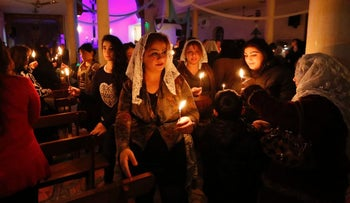 Christians celebrate Christmas Mass in Baghdad, 2014. Women, some of them with lace scarves draped over their heads, carry lit candles in a darkened church.