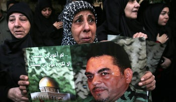 A Lebanese Shi'ite woman weeps as she holds a portrait of Hezbollah high-profile militant Samir Kuntar, December 21, 2015.