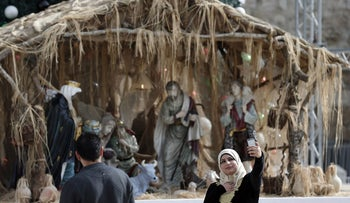 A muslim woman takes a selfie picture in front of a Christian manger, in the West Bank city of Bethlehem on the Manger Square near the Church of the Nativity,  on December 16, 2015.