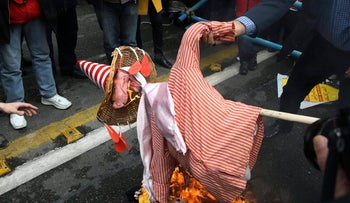 An Iranian demonstrator setting an effigy of the U.S. President Barack Obama on fire, during an annual rally in front of the former U.S. Embassy in Tehran, marking 36th anniversary of the seizure of the embassy by militant Iranian students, Iran, Wednesday, October 4, 2015.