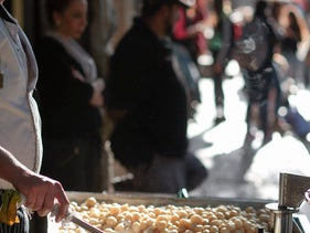 Anan Hawidi makes awama outside his family's pastry shop in Nazareth.