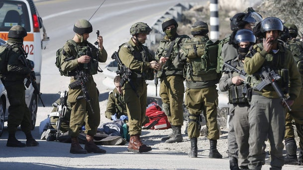 Israeli soldiers work around the body of a Palestinian assailant after he was shoot dead in the West Bank city of Hebron, Thursday, Dec. 24, 2015.