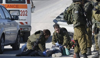 Israeli soldiers work around the body of a Palestinian assailant after he was shot dead in the West Bank city of Hebron, Thursday, Dec. 24, 2015.