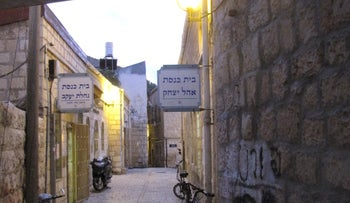 The twin synagogues of Nahalat Shiva in central Jerusalem, one on each side of the cobblestone pedestrian street, at sunset.