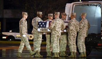 A U.S. Air Force carry team moves a transfer case with the remains of fallen Staff Sgt. Chester J. McBride who was one of the six U.S. troops killed by a suicide bomber near Bagram air base in Afghanistan, December 23, 2015.