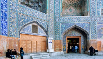 Women chatting along the old walls of the Imam (Shah) Mosque in Iran. The Mosque was built in 1611 by the Shah Abbas I of Persia.